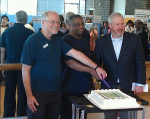 "Councilmember Richard Conlin, Councilmember Larry Gossett, and Mayor Mike McGinn cut the ""Coverage is Here"" cake, at Garfield Community Center."