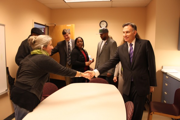 Vera Johnson of White Center shakes hands with King County Executive Dow Constantine, shortly after she filled out her paperwork to enroll on Washington Healthplanfinder, on the morning of Oct. 1, the first day of enrollment. Just behind the Executive is Ben Smith of Seattle.