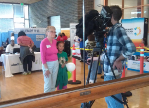 Patty Hayes of PHSKC gets help facing the Q13 TV camera, at Garfield Community Center in Seattle.
