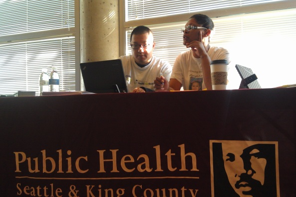 Rod Kim of Public Health assists Chrystale Holiwell enrolling in Washington Healthplanfinder, at Garfield Community Center in Seattle.